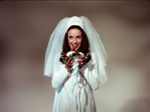 1967 smiling bride with long brown hair tossing bouquet towards camera in studio / industrial