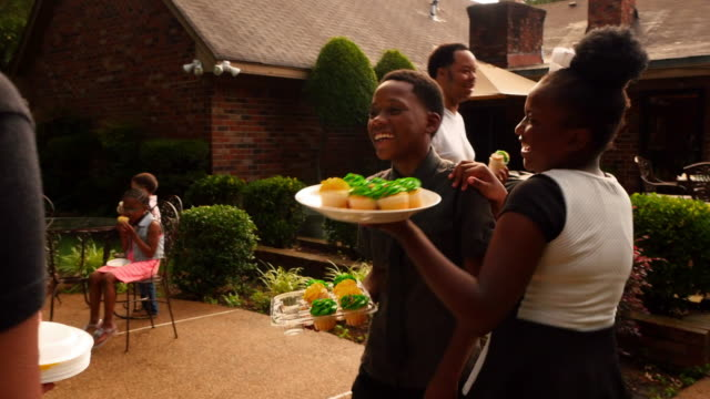 MS Smiling brother and sister serving cupcakes to friends and family during outdoor celebration