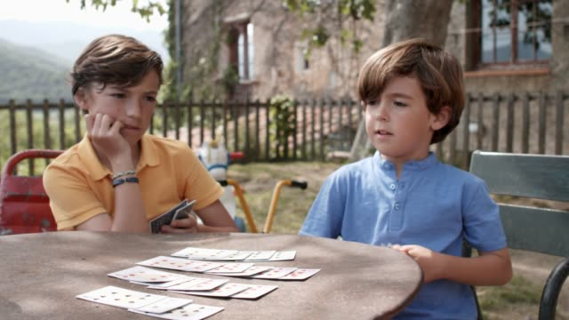 vídeos de stock, filmes e b-roll de sorrindo irmãos jogando cartas na mesa no quintal - suit