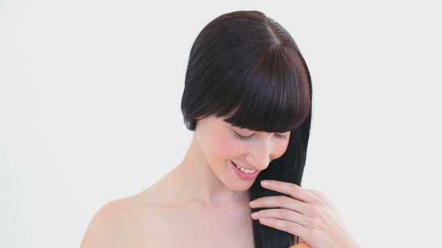 stockvideo's en b-roll-footage met smiling brunette brushing her hair - haar borstelen
