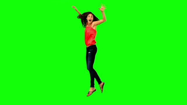 Smiling brunette jumping in slow motion
