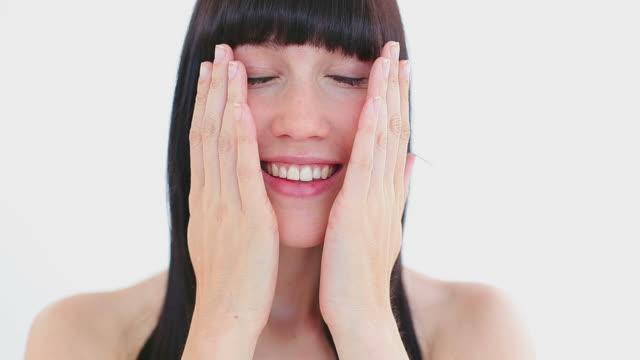 Smiling brunette massaging her two cheeks