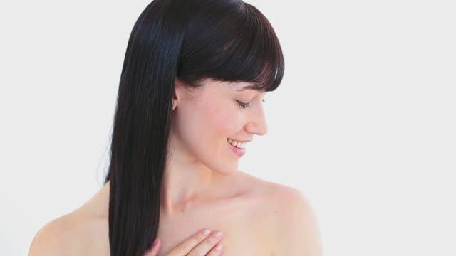 Smiling brunette woman massaging her shoulder