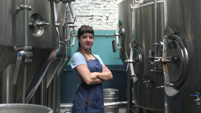 smiling buenos aires female craft beer expert in brewery - arms crossed stock videos & royalty-free footage