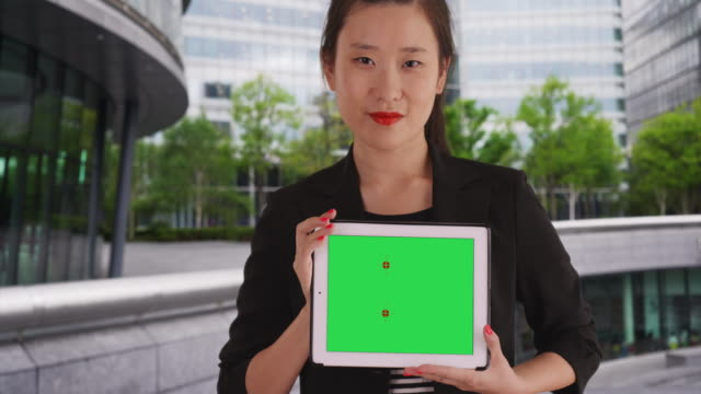 Smiling business lady holding handheld tablet with greenscreen outside office