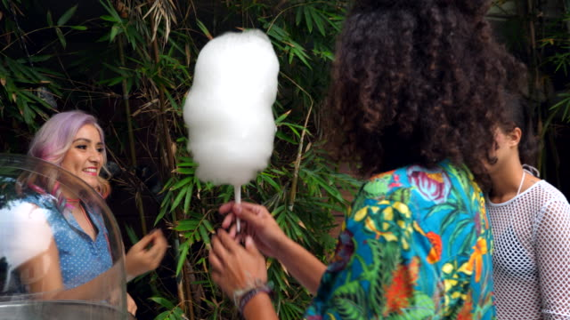 ms smiling business owner handing cotton candy to customer during party - anticipation stock-videos und b-roll-filmmaterial