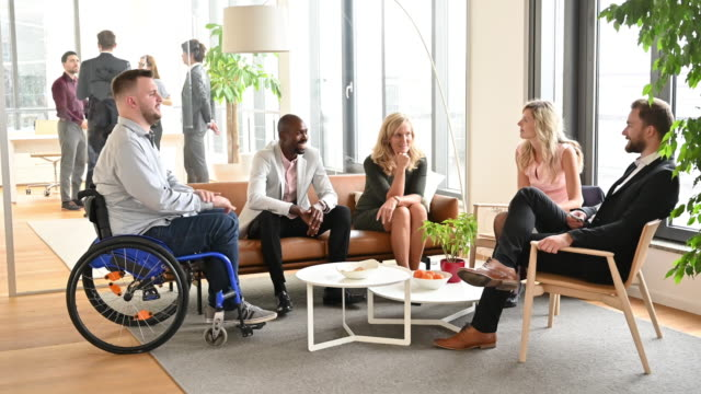 smiling business people relaxing and talking in office lobby - disability stock videos & royalty-free footage