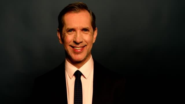 stockvideo's en b-roll-footage met lachende zakenman tegen de grijze achtergrond - formeel portret