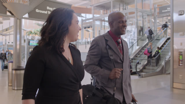 vídeos y material grabado en eventos de stock de smiling businessman and woman walk through airport terminal towards gate. pan around. - comunidad global