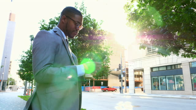 MS LA Smiling businessman checking smartphone on city sidewalk