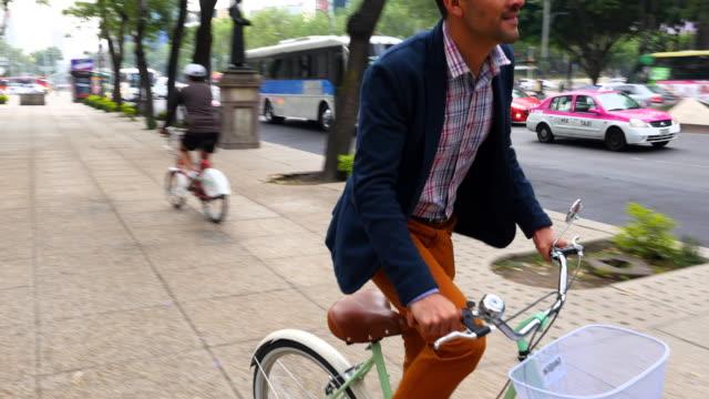 MS TS Smiling businessman commuting on bike down sidewalk of city street