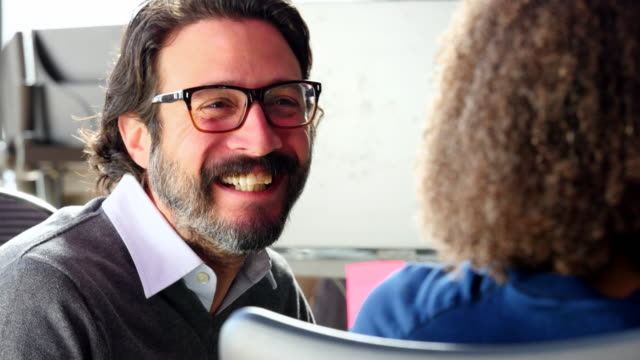 MS Smiling businessman in discussion with businesswoman in high tech office