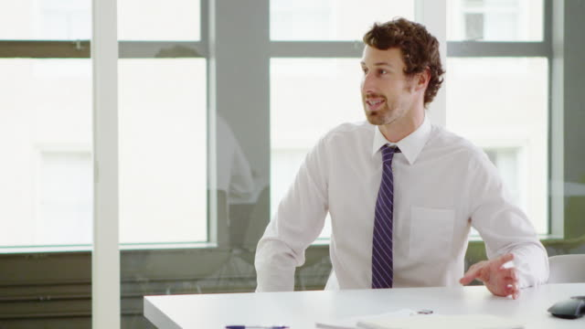 vídeos de stock e filmes b-roll de ms smiling businessman in discussion with colleague at conference room table - camisas