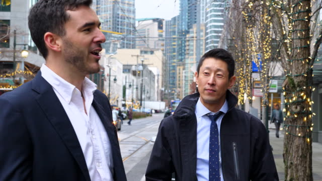 MS Smiling businessman in discussion with colleague while standing on downtown street