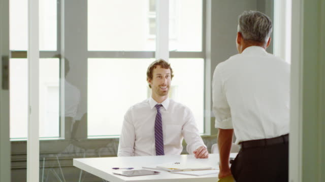 MS Smiling businessman in discussion with coworker standing at table in office