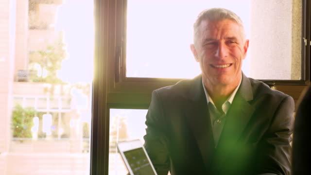 vídeos y material grabado en eventos de stock de ms smiling businessman in discussion with coworkers during meeting in office - empleo y trabajo