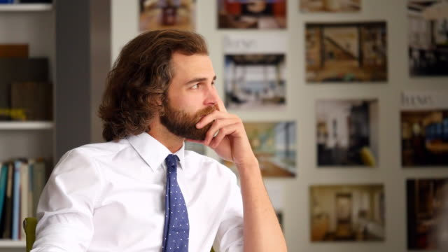 MS Smiling businessman listening during meeting in office