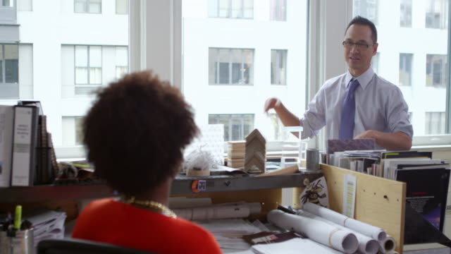 MS Smiling businessman standing at office workstation in discussion with coworker