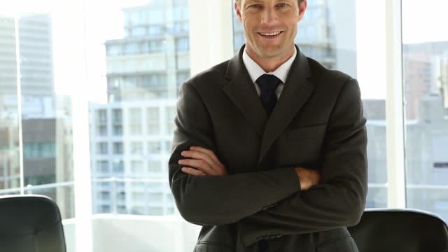 vidéos et rushes de smiling businessman standing by window - costume complet