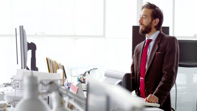 MS smiling businessman standing in discussion at table in office workstation