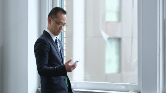MS Smiling businessman standing near window in office looking at smartphone and laughing