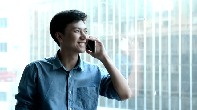 smiling businessman talking on cell phone in the meeting room - asian chance stock videos & royalty-free footage