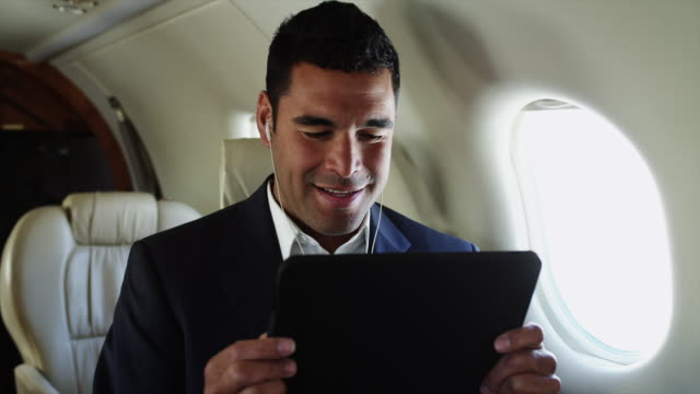MS Smiling businessman using digital tablet in airplane / Spanish Fork, Utah, USA