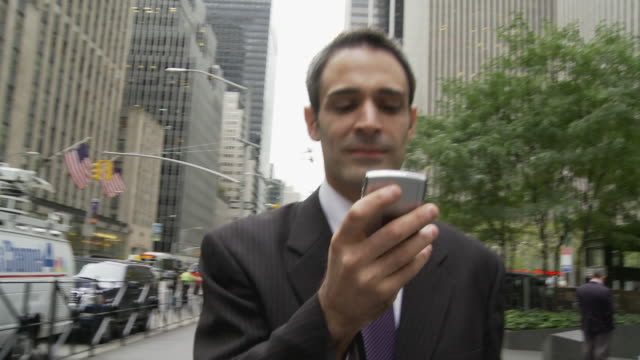 CU SHAKY Smiling businessman using smart phone on busy street / New York City, New York, USA