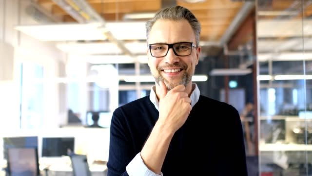 smiling businessman with hand on chin in office - spectacles stock videos & royalty-free footage