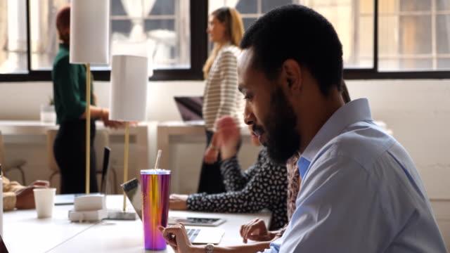 vidéos et rushes de ms smiling businessman working on laptop in coworking office - adulte d'âge moyen