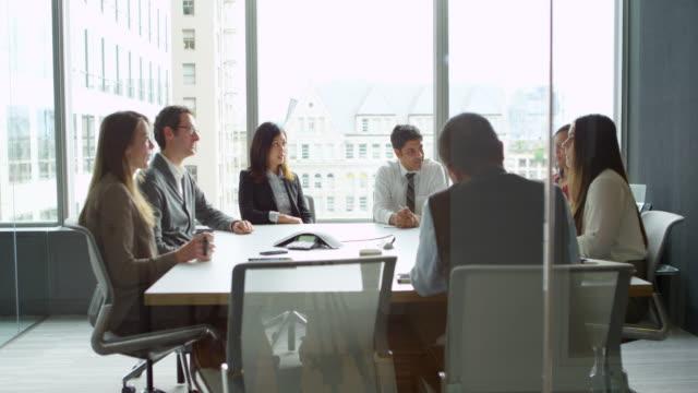 vídeos y material grabado en eventos de stock de ms smiling businesspeople laughing together during meeting in office conference room - buenas noticias