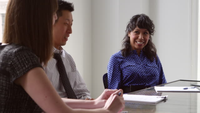 MS Smiling businesspeople listening to coworker during team meeting in office conference room
