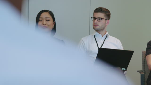 lächelnde geschäftsfrau inmitten von kollegen in derversammlung - wissenschaft und technik stock-videos und b-roll-filmmaterial