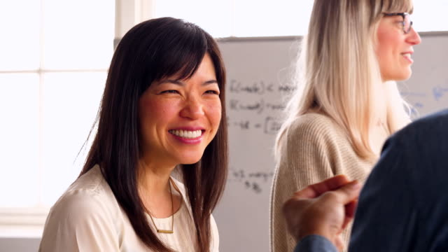 ms smiling businesswoman discussing project with coworker in design studio - 談笑する点の映像素材/bロール