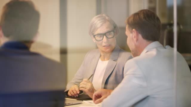 stockvideo's en b-roll-footage met glimlachende zakenvrouw bespreken met collega 's - medewerkerbetrokkenheid