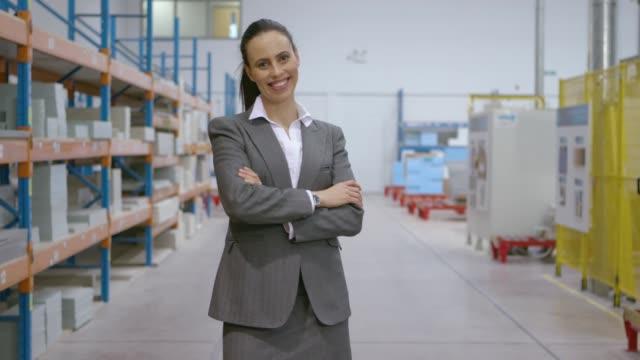 vídeos y material grabado en eventos de stock de empresaria sonriente en un almacén de distribución - propietario