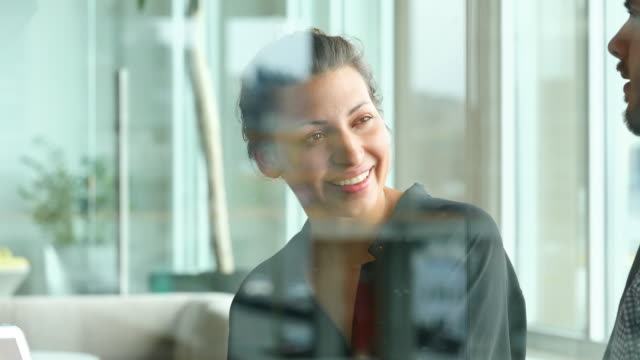 ms smiling businesswoman in discussion with colleagues during project meeting in office - business relationship stock videos and b-roll footage