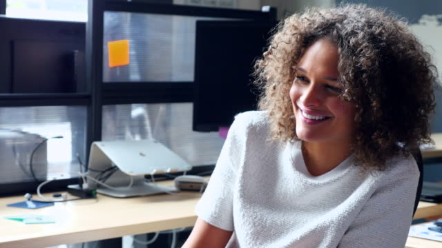 MS Smiling businesswoman in discussion with coworker at workstation in high tech office