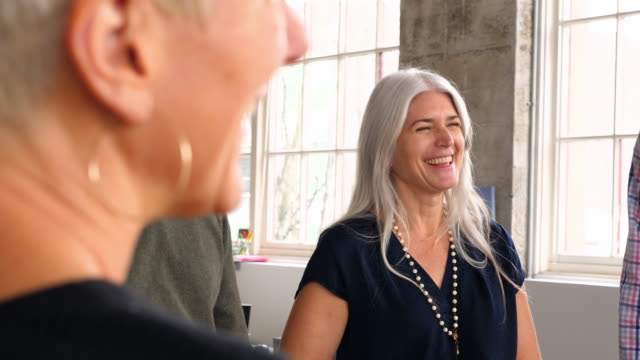 MS Smiling businesswoman in discussion with coworker during project planning meeting in office