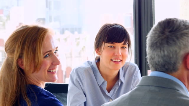 MS Smiling businesswoman in discussion with coworkers during meeting in conference room