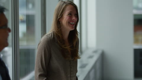 vídeos y material grabado en eventos de stock de ms smiling businesswoman laughing with coworkers during meeting in office - contento