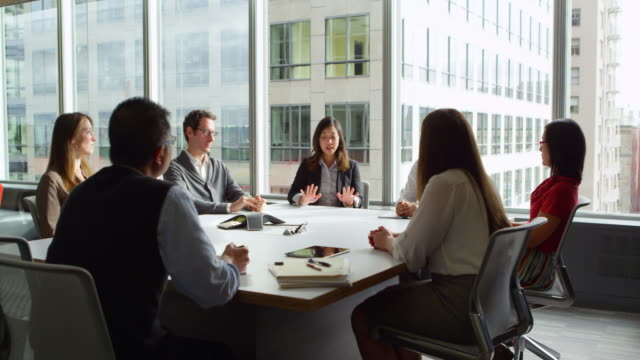 ms smiling businesswoman leading discussion during meeting with colleagues in office conference room - meeting stock-videos und b-roll-filmmaterial