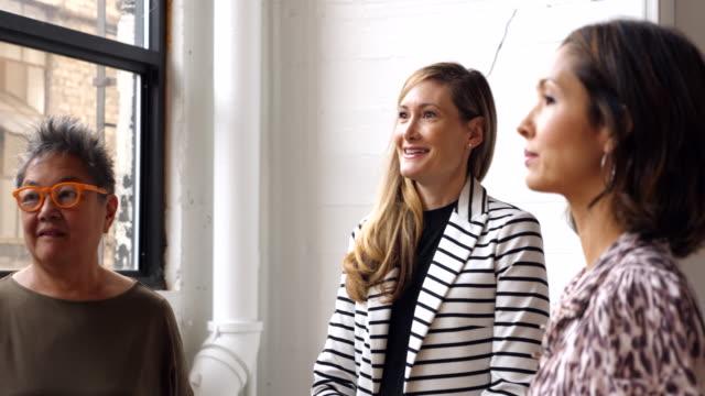 vidéos et rushes de ms smiling businesswoman leading meeting with coworkers in office - tenue d'affaires formelle