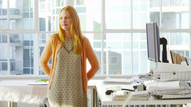 MS smiling businesswoman leaning against table in office workstation
