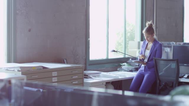 MS Smiling businesswoman leaning on desk in workstation working on digital tablet
