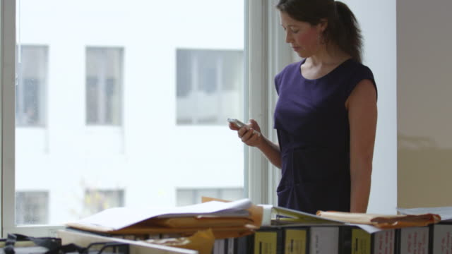 MS TU Smiling businesswoman looking at smartphone near window in office