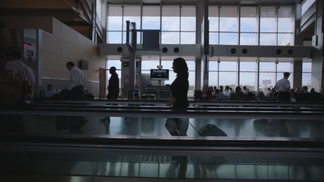 stockvideo's en b-roll-footage met slo mo. smiling businesswoman travels along moving walkway through airport terminal. - zakenreis