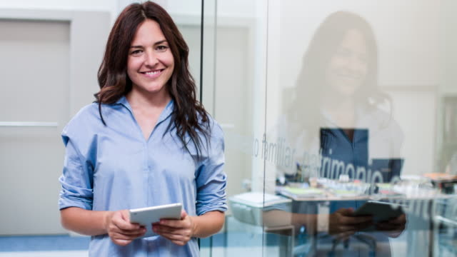 Smiling businesswoman using digital tablet while leaning on glass wall