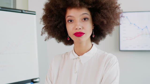 smiling businesswoman with afro hair standing in office by flipchart - big hair stock videos & royalty-free footage