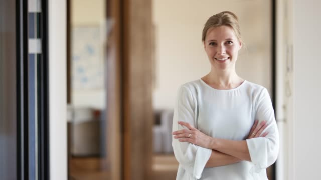 smiling businesswoman with arms crossed in office - mid adult stock videos & royalty-free footage